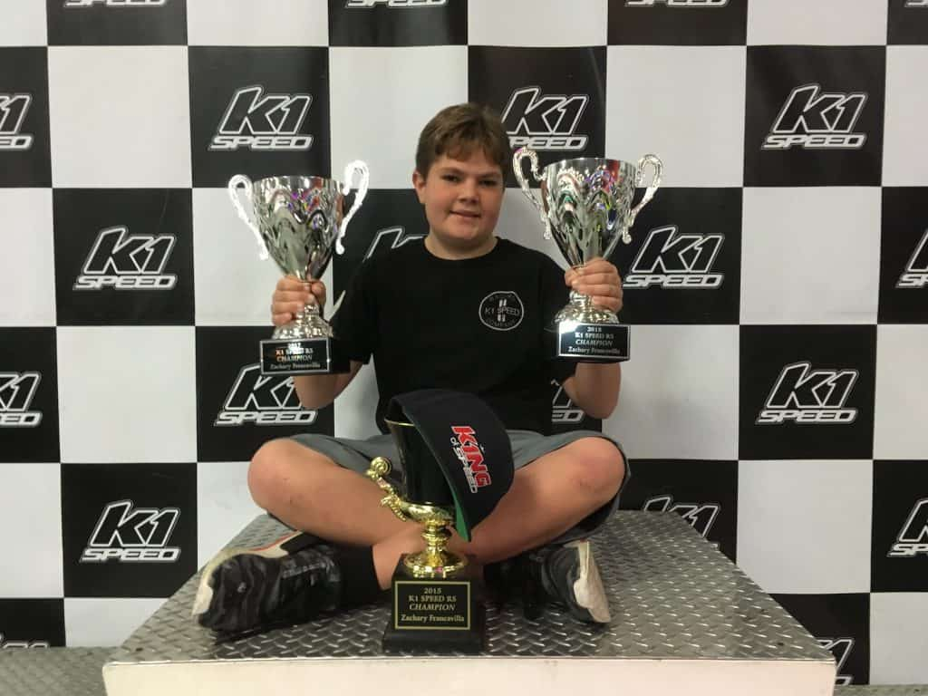Zachary Francavilla sits on the podium at K1 Speed with his trophies