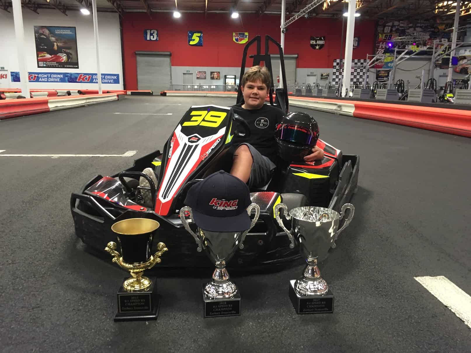 Zachary Francavilla sits in a gokart at K1 Speed surrounded by his trophies