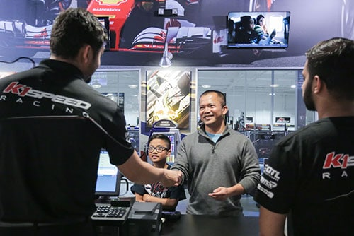 cashier hands a membership card to a customer at k1 speed
