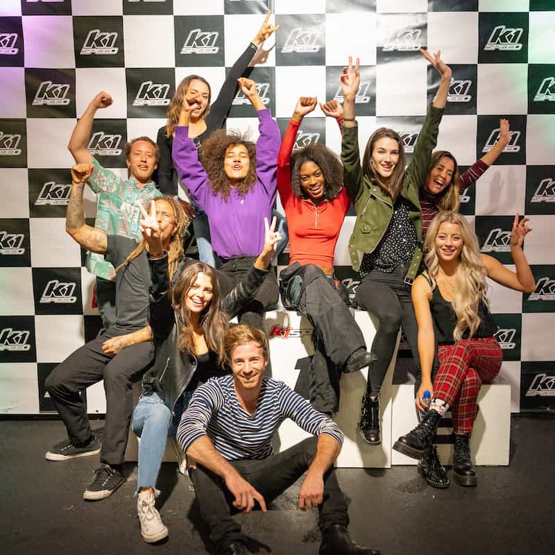 a group of people pose at a k1 speed podium