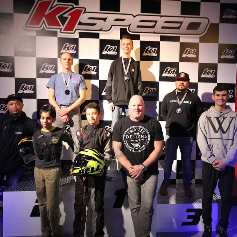 Paul Tracy stands by the K1 Speed indoor go kart racing podium in Toronto, Canada