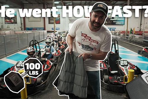 man holds weight vest with scale and go karts in background