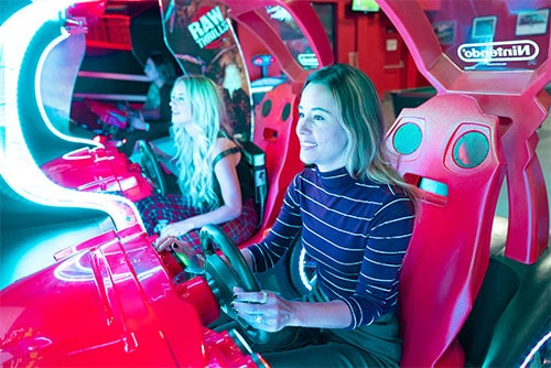 two girls play an arcade game at k1 speed